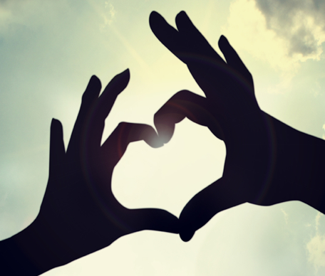 silhouette of hands forming a heart